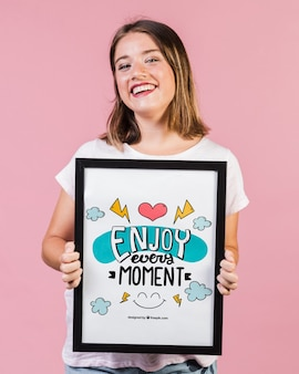 Mujer joven sonriente que muestra una maqueta del marco