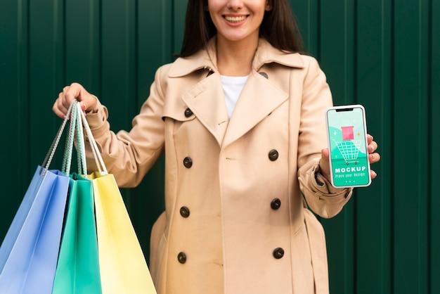 Mujer joven sosteniendo bolsas de la compra y una maqueta de teléfono