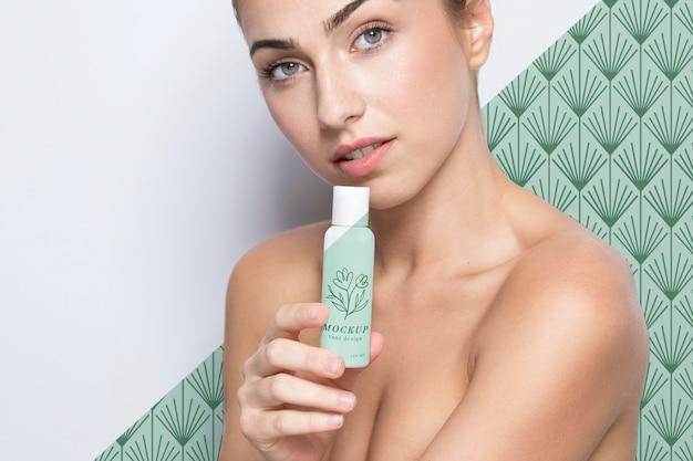 Mujer joven sosteniendo una maqueta de productos para el cuidado de la piel