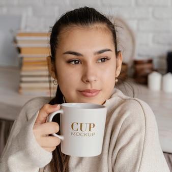Mujer joven sosteniendo una taza de maqueta