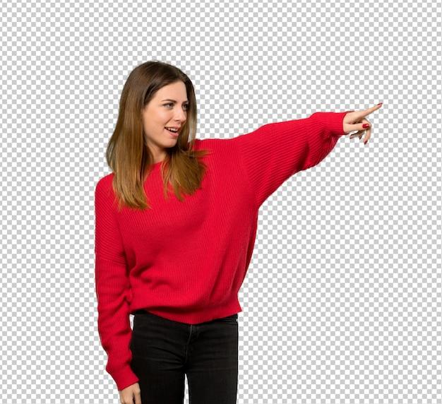 Mujer joven con suéter rojo apuntando lejos