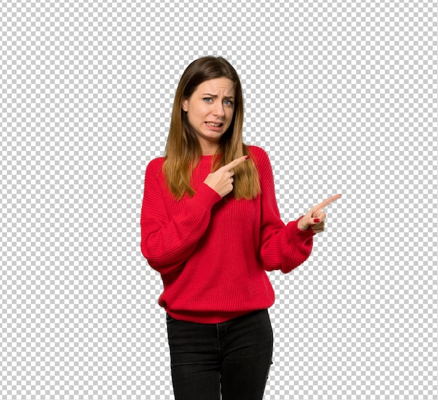 Mujer joven con suéter rojo asustada y apuntando hacia un lado.