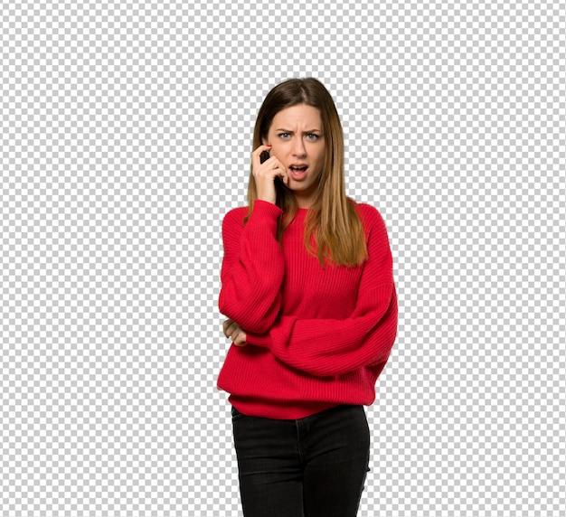 Mujer joven con suéter rojo sorprendida y conmocionada