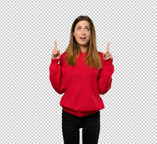 Mujer joven con suéter rojo sorprendido y apuntando hacia arriba