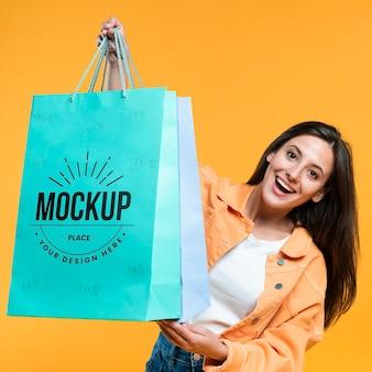 Mujer joven, tenencia, bolsas de compras, maqueta