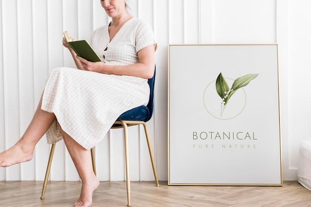 Mujer leyendo un libro sentada junto a una maqueta de marco botánico
