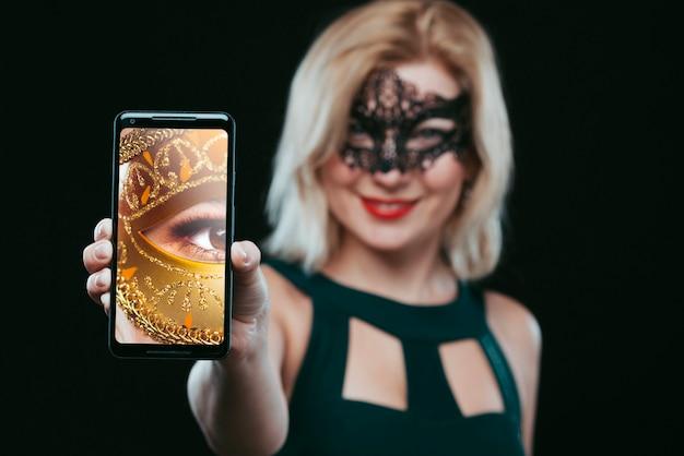 Mujer con máscara de carnaval enseñando maqueta de smartphone