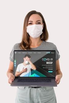 Mujer con máscaras sosteniendo portátil