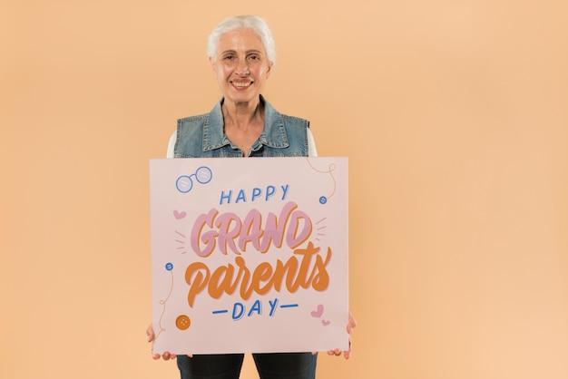 Mujer mayor presentando tabla para el día de abuelos