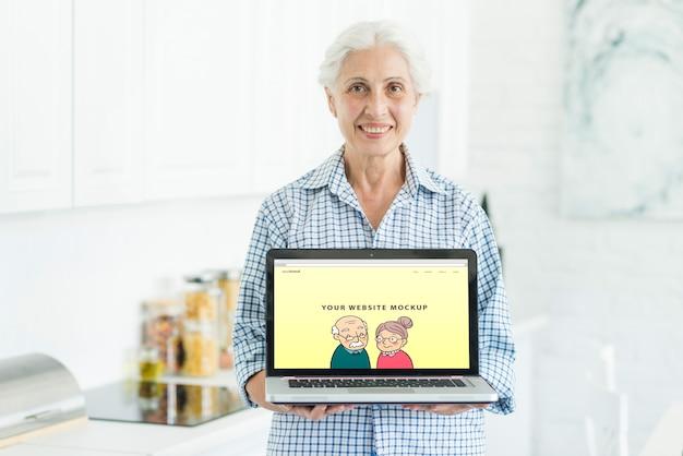 Mujer mayor sujetando mockup de portátil