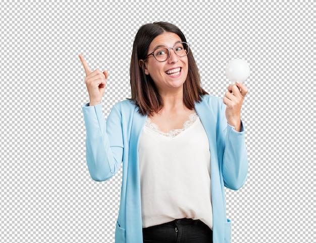 Mujer de mediana edad alegre y emocionada, apuntando hacia arriba, sosteniendo una bombilla como símbolo de idea, imaginación, fluidez mental y sabiduría, foto inspiradora