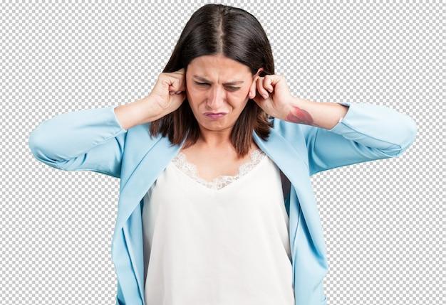 Mujer de mediana edad cubriendo los oídos con las manos, enojada y cansada de escuchar algún sonido