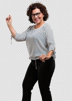 Mujer de mediana edad escuchando música, bailando y divirtiéndose, moviéndose, gritando y expresando felicidad, concepto de libertad