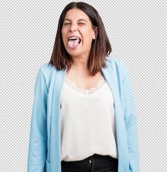 Mujer de mediana edad, expresión de confianza y emoción, divertida y amigable, mostrando la lengua como un signo de juego o diversión.