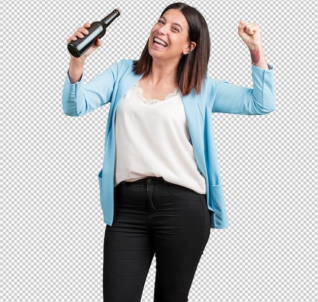 Mujer de mediana edad feliz y divertida, que sostiene una botella de cerveza, se siente bien después de un intenso día de trabajo, lista para ver un partido de fútbol en la televisión.