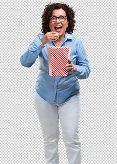 Mujer de mediana edad feliz y fascinada, sosteniendo un cubo de palomitas de maíz a rayas, sorprendida por la nueva película, con los ojos abiertos y una expresión de admiración.