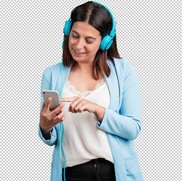 Mujer de mediana edad relajada y concentrada, escuchando música con su teléfono móvil.