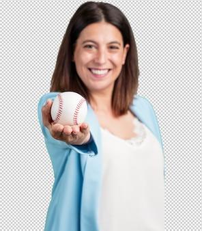 Mujer de mediana edad, sonriente y feliz, sosteniendo un balón de fútbol, actitud competitiva