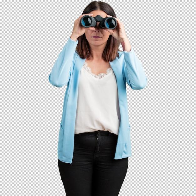 Mujer de mediana edad sorprendida y sorprendida, mirando con binoculares en la distancia