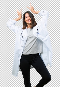Mujer médico con estetoscopio hace emoción de cara divertida y loca