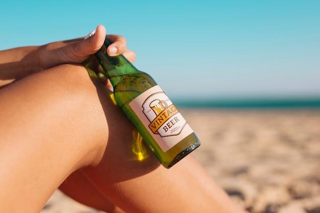 Mujer con mockup de botella de cerveza en la playa