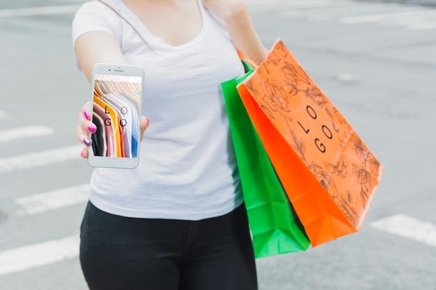 Mujer con mockup de smartphone y bolsas de compra