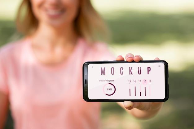 Mujer mostrando un teléfono con una pantalla de maqueta al aire libre