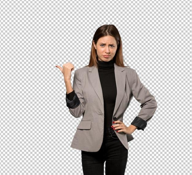 Mujer de negocios infeliz y apuntando hacia el lado.
