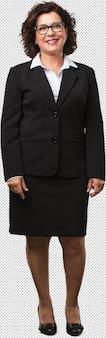 Mujer de negocios de mediana edad de cuerpo completo alegre y con una gran sonrisa, confiada, amable y sincera, que expresa positividad y éxito.