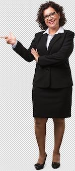 Mujer de negocios de mediana edad de cuerpo completo apuntando hacia un lado, sonriendo sorprendida presentando algo, natural y casual