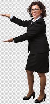 Mujer de negocios de mediana edad de cuerpo completo sosteniendo algo con las manos, mostrando un producto, sonriendo y alegre, ofreciendo un objeto imaginario