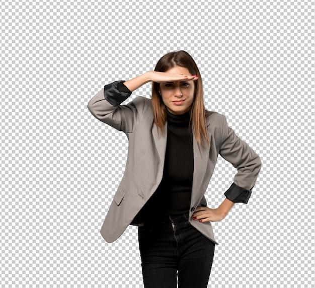 Mujer de negocios que mira lejos con la mano para mirar algo