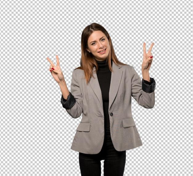 Mujer de negocios que sonríe y que muestra la muestra de la victoria con ambas manos