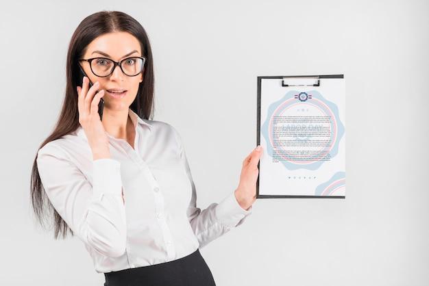 Mujer de negocios sujetando maqueta de portapapeles para el día de trabajo PSD gratuito