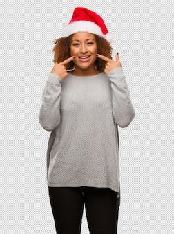La mujer negra joven que lleva un sombrero de santa sonríe, señalando la boca