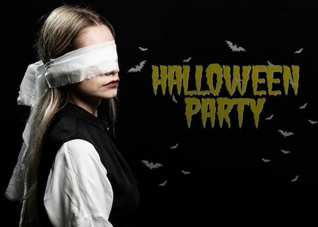 Mujer con los ojos atados con un disfraz de halloween de tela blanca