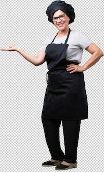 Mujer de panadero de mediana edad de cuerpo completo sosteniendo algo con las manos, mostrando un producto, sonriente y alegre, ofreciendo un objeto imaginario