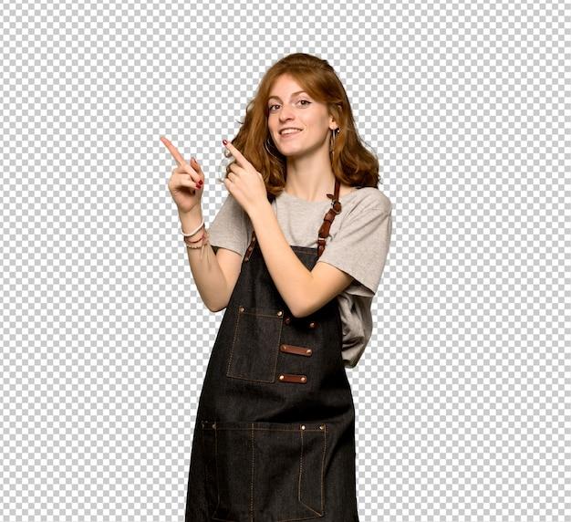 Mujer pelirroja joven con delantal apuntando con el dedo índice y mirando hacia arriba