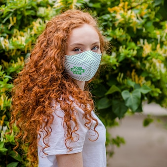 Mujer de pelo rojo con mascarilla protectora médica