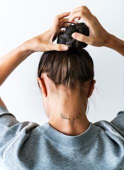 Mujer poniendo su cabello en un moño