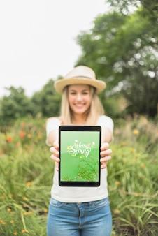 Mujer presentando maqueta de tableta en la naturaleza