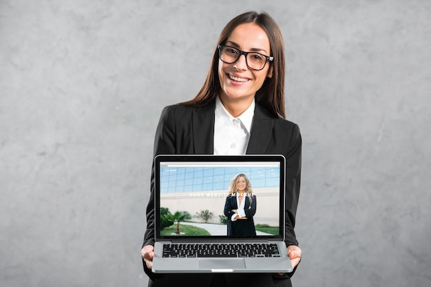 Mujer presentando mockup de portátil