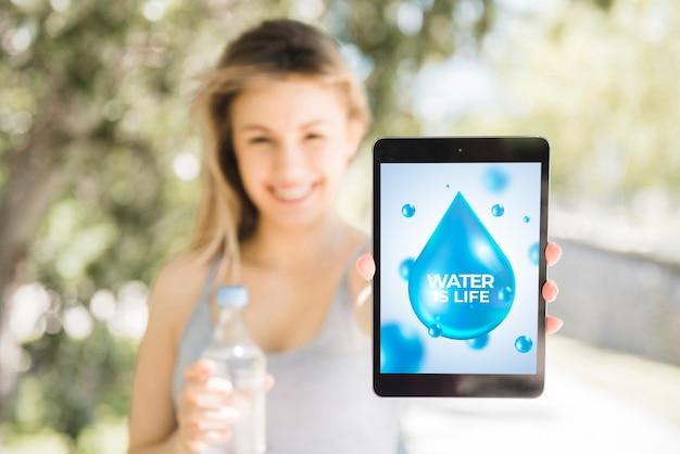 Mujer presentando mockup de tableta con concepto de agua
