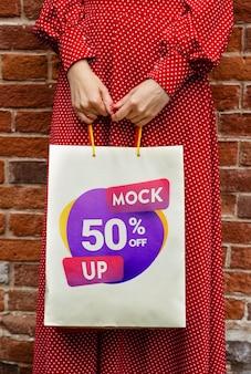 Mujer de primer plano sosteniendo bolsas con descuento