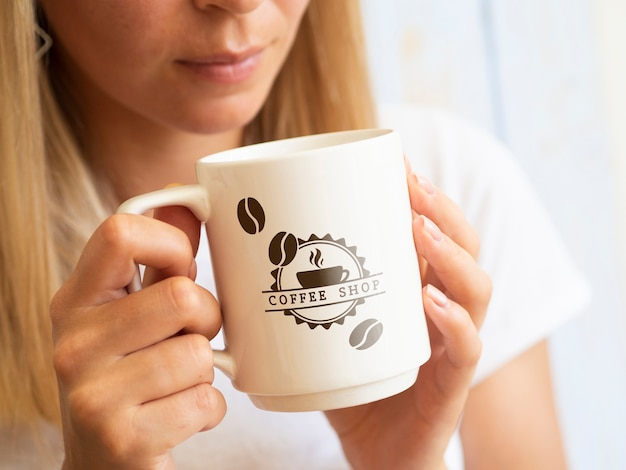 Mujer que quiere beber de una maqueta de taza de café
