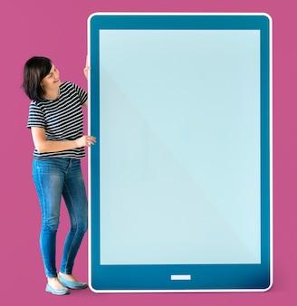 Mujer que sostiene una maqueta azul de la tableta