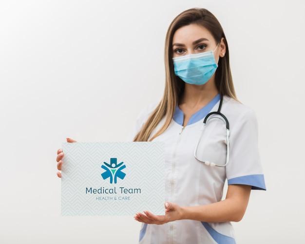Mujer que sostiene la tarjeta médica de la maqueta
