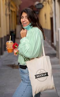Mujer que tiene una bolsa textil de maqueta
