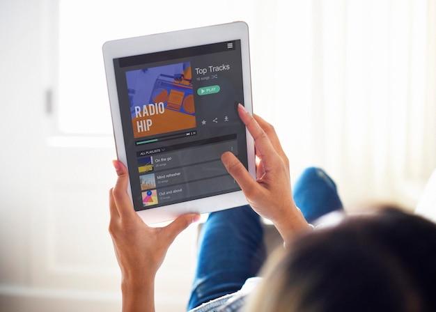 Mujer que usa una tableta digital y un concepto de radio de música