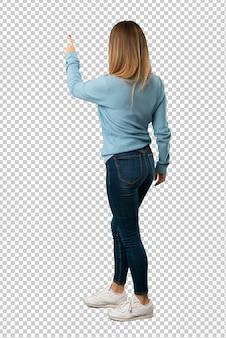 Mujer rubia con camisa azul apuntando hacia atrás con el dedo índice